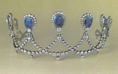 A sapphire and diamond tiara with at least nine large sapphires, surrounded by diamond, linked at the base by overlapping scrolls