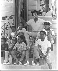 Huey Newton of The Black Panther Party taking a picture with the youth.