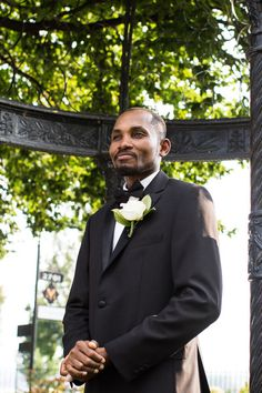 Classic modern groom outfit idea - black tuxedo with black bow tie + white rose boutonniere  {De Joy Photography}