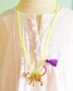 Cat Necklace. Tassel Necklace. Gifts for Cat Lovers.  {DESCRIPTION} All of the necklaces are handmade using recycled plastic animal toys and painted and sealed with care in bright, fun non-toxic colors. Each necklace is accented with a trendy bright tassel on soft satin cording. This listing is for the gold cat with a bubblegum pink tail and ears on satin neon yellow cording and purple tassel. The cat measures approximately 2 long and 1 tall.  {MEASUREMENTS} This necklace measures 24, making…