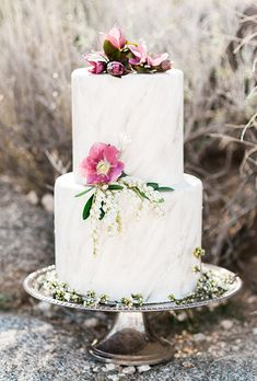 Brides.com: . A two-tiered wedding cake with subtle marble detailing, topped with fresh flowers, created by Sweet Lydia's of San Diego.