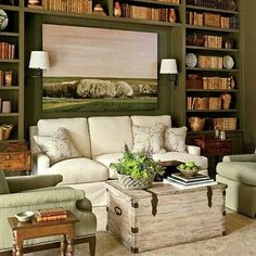 Cozy living room with built in bookshelves surrounding a plush sofa. Minus the light wood bench and flowers