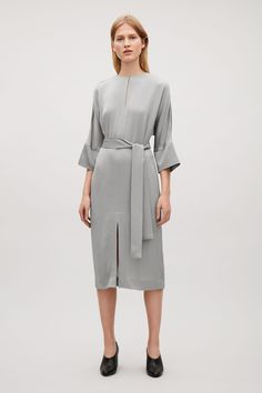 Designed with soft, relaxed proportions, this kimono-sleeved dress is made from a shiny satin fabric with a tactile, crepe finish. Coming in at the waist, tied with a fabric belt, it is completed with simple in-seam pockets, a hidden side zip and a neat round neckline with a subtle slit and hook fastening.