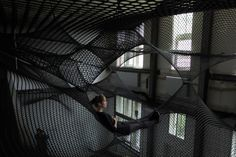 "architectural art installation. by numen. called net. ""transparent landscapes create a layering of levels inspired to reinvent the concept of a backyard and to recreate the sensation of flying. create a public balcony or transparent space, accessible to a population alienated by suburban living, reconnecting backyard to form community spaces."""