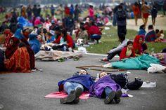 En esta imagen proporcionada por la agencia de noticias china Xinhua, touristas duermen al aire libre tras un terremoto en Katmandú, Nepal, el 26 de abril de 2015. (Pratap Thapa/Xinhua via AP)