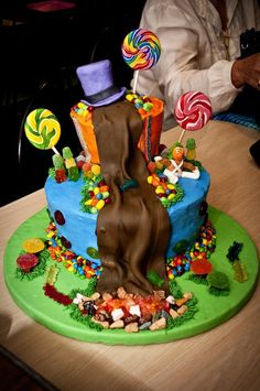 My son's 5th birthday cake. Willy Wonka design cake with chocolate/chocolate-chip cake with fudge filling and buttercream icing. The hat is rice krispie treat covered in fondant, the chocolate river and the Oompa Loompa are fondant and everything else is candy. The only thing inedible on this cake are the lollipop sticks!