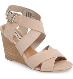 Wide straps overlap on this graceful standby sandal set on a stacked wedge heel.