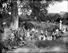 Barracks Lane, Cowley, Oxford, Oxfordshire. Children playing in the sheep-washing pool on a hot summer's day. Note how the children in smarter clothes are sat watching, not joining in. 1914