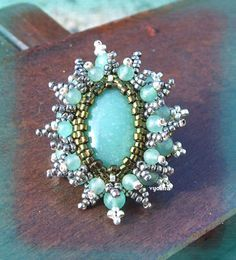 A pattern for pendant or ring or brooche Aventureine by Vyolina.  (Part 1 of 4).  U need:    1 cabochon or button 18×13 mm    10 round beads 4 mm    10 round beads 3 mm    seed beads (delica) 11\0    seed beads 15\0  - See more at: http://beadsmagic.com/?p=626#more-626