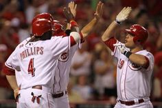 Left to right Cincinnati Reds Brandon Phillips (4), Todd Frazier (21) and Chris Heisey (28) congratulated Devin Mesoraco (39) at home plate after Mesoraco hit a grand slam home run to left field against the Atlanta Braves in the 6th inning.