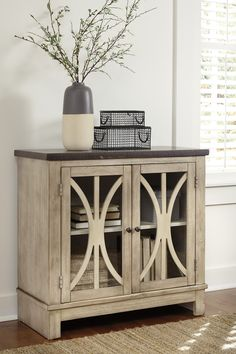 With curving door fronts and a eye-catching two-tone finish, the Vennilux accent cabinet is the ideal blend of grace and functionality. Clear glass inserts protect and display the contents you store inside.