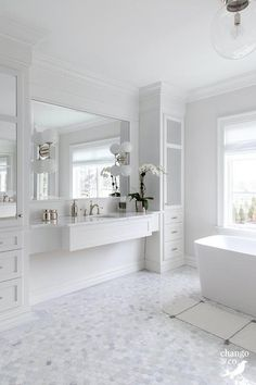 White shaker drawers accented with polished nickel pulls are built-in beneath mirrored cabinets positioned flanking a white wall mount sink vanity.