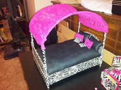 Barbie canopy bed made from a cereal box and card board wrapped in duct tape. The 4 posts are pencils the canopy is handles off of gallon ice cream buckets with a piece of lace out of a shirt I sewed to it. The pillows I sewed. From old pieces of clothes except the zebra ones they are wrapped with duct tape.