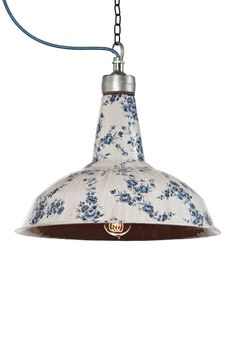An industrial pendant lamp with a soft white and blue floral ceramic casing.