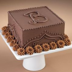Add a Chocolate Monogram Cake - Dignified and Impressive--and who does not love chocolate? Two-tone pompon flowers surround this dark and delicious cake. Perfect choice for a groom's cake.