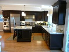 Kitchen with espresso stained cherry cabinets, granite counter tops and red oak hardwood flooring