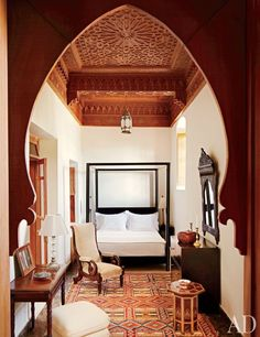 A Berber carpet echoes the geometric ceiling of a bedroom. The mirror is Syrian, and the bed and chest of drawers are Grassi designs.