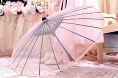 Turn a party umbrella (available in the Card and Party Department) into a romantic wedding parasol. First, remove the paper and paint the frame as desired. Then, cut a circle of tulle to stretch across the ribs—be sure to cut a small hole in the center to accommodate the finial. Use hot glue to secure the fabric at the tip of each rib, and finish with a pretty trim.