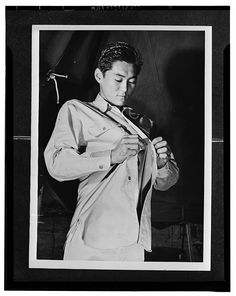Kauai District, Territory of Hawaii. Mitsuru Doi, first American of Japanese ancestry to volunteer for induction into United States Army, buttoning his uniform shirt.    CREATED/PUBLISHED  1943 Mar.