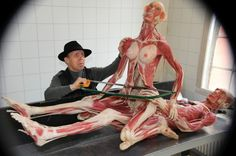 Hagens holds a saw against a female human cadaver, which sits on top of a male cadaver, making a pose of making love