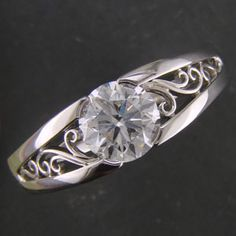 Custom platinum split shank tension style mounting holding a round diamond with filigree curls on each side of the center stone in 'V' shaped top face panels.