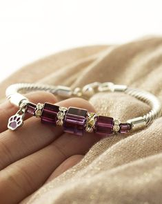 Radiant crystals and the solid look of silver-tone cable combine for purple paw bracelet that is equal parts beauty and strength.