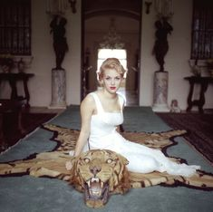 Lady Daphne Cameron (Mrs. George Cameron) on a tiger skin rug in the trophy room at Laddie Sanford's home in Palm Beach, Florida. Photographed by Slim Aarons, 1959.