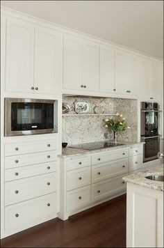 Love the granite with this cream-colored cabinetry. Placement of microwave, cooktop, and ovens.