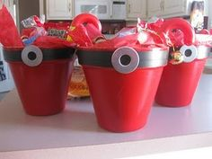 The clay pot is painted red, the black stripe is electrical tape with a washer hot glued on, filled with holiday treats. Too cute!!