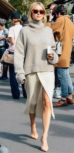 Fashion blogger Pernille Teisbaek wears a cream oversized sweater, slit sweater skirt, and pointed toe-heels