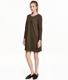 Dark khaki. Long-sleeved, A-line dress in thick jersey with side pockets, concealed zip at back, and slits at cuffs.