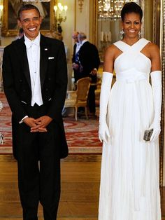 LA ELEGANCIA DE LOS GUANTES    Desde que Barack Obama asumió la presidencia, hemos visto a la primera pama desfilar con diseños sin mangas y lucir sus torneados brazos. Para la recepción celebrada en el 2011, en el Palacio de Buckingham, en Londres, Michelle Obama mantuvo esta preferencia y escogió este modelo en blanco del diseñador Tom Ford, de escote cruzado, al que le añadió unos guantes por encima de los codos que acentuaron la elegancia del vestido.