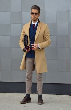 Opt for a camel overcoat and grey skinny jeans for your nine-to-five. Round off this look with brown leather boots.  Shop this look for $369:  http://lookastic.com/men/looks/overcoat-and-double-breasted-blazer-and-tie-and-skinny-jeans-and-boots-and-dress-shirt-and-gloves/2086  — Camel Overcoat  — Navy Double Breasted Blazer  — Burgundy Tie  — Grey Skinny Jeans  — Brown Leather Boots  — White Dress Shirt  — Burgundy Leather Gloves