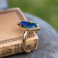 The navette shaped ring is centered with an oval, black opal cabochon in a four-prong setting. The opal is accented by two bead set, round single cut diamonds. The ring measures at the top, rises above the finger, tapering to wide a Diamond Shapes, Diamond Cuts, Aquamarine Jewelry, Black Opal, Opal Rings, Cocktail Rings, Engagement Rings, Opals, Yellow