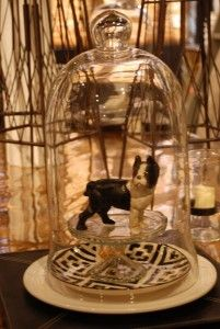 I really like to decorate with figurines, like this cute little dog statue. Using them as the focal point or as a little surprise to reward the careful viewer. We added some mirth to this dining table display with this Boston terrier under glass.  Putting fanciful items under a cloche increases their star power. If you're not one for figurines, you could opt for a little potted succulent or a funny snapshot of a loved one in a little frame. (Nell Hill's)