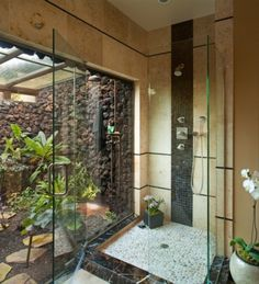 Shower with a garden view. Love the pebble tiles on the shower floor.