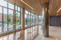 Column in Stainless Steel with Sandstone finish and Kalahari Impression pattern, and Profile One Information Kiosks shown in single-mast configuration with wood table tops at Salem State University, Salem, Massachusetts