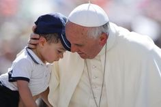 Pope Francis hugs a child as he arrives to lead the weekly audience in Saint Peter's Square at the Vatican, June 19, 2013. REUTERS-Stefano Rellandini