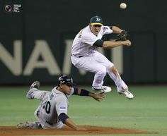 Oakland Athletics shortstop Pennington throws the ball to first base as Seattle Mariners Olivo slides into second base to break up a double play during their season opening MLB baseball game in Tokyo. Toru Hanai/REUTERS