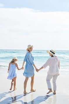 Mother, daughter and grandmother walking by the sea, rear view