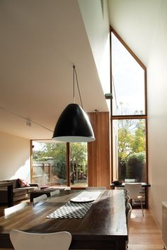 """An asymmetrical, domestic take on a cathedral window marks where the roof """"leaps away"""" at a double-height void in the addition. Interior Architecture, Interior And Exterior, Interior Design, Gable Window, Gable Roof, 1960s House, Victorian Homes, Victorian Terrace, Roof Light"""