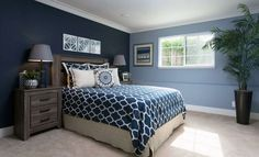 Two blue colors bedroom with picture window white molding and beige carpet