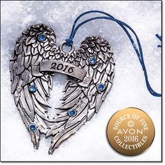 """2016 Angel Wings Pewter Ornament†† This dated pewter ornament features a detailed angel wings design adorned with """"2016"""" and shiny blue faux stones on one side, and the Avon Collectibles logo on the other. String with tassel for hanging. Comes in a navy velvety pouch. 3"""" H x 2 1/4"""" W. Imported. Item#: 959-012 Brochure: $9.99"""