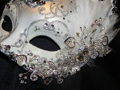 This mask is such a unique shape, it is truly one of a kind. The mask is beautifully decorated in a silver glitter pattern on a white and silver base colour. Mask is trimmed in silver sequin trim, dotted with tons of clear gems and is attached to a ribbon for ease in hands free wearing. Features white coque feathers and is topped off with a silver rhinestone flower vine as the centerpiece.    Wide variety of masks available in my store. Contact me for a custom order, they are my specialty