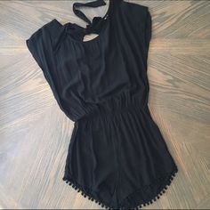 HP | Romper w/ Pom Pom Hem NWOT. Love this! Just have never worn it. Pom Pom's dangling from the hem. Cut out on the back with bow. Black, not see through. Stretch waistband. I did cut the tag out when I tried it on at home because it showed. 110% positive on size small. Entire length 31.5 inches. Waistband to crotch is 13.5 inches. Boutique Dresses Mini
