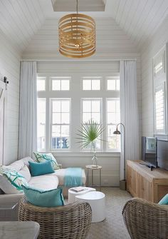 Beach style living room features a taupe sectional lined with turquoise blue pillows facing a low wood tv cabinet illuminated by a gold striped drum pendant hanging from a tray shiplap ceiling.