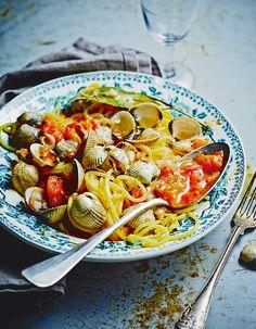 Recette Spaghettis aux coques : Faites tremper 1,5 litre de coques dans un grand saladier d'eau fraîche salée deux heures avant de cuisiner, pour qu'elles « crachent » leur sable. Entaillez le dos de 3 petites tomates avec un couteau, sans trop entamer la chair, et plongez-les dans une casse...