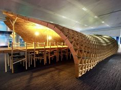 At London's Bloomberg headquarters, the Pupa installation (by Liam Hopkins/Lazerian) is made of 3972 reclaimed cardboard pieces and pallets. The cave-like structure shelters a rectangular dining table where staff enjoy lunch.