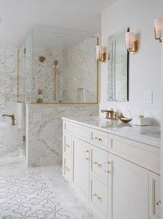 Ivory mosaic floor tiles framed by marble tiles are positioned in front of an ivory dual washstand boasting brass and glass pulls and a white quartz countertop fitted with round his and her sinks with gold faucets. Bathroom Layout, Bathroom Interior Design, Home Interior, Interior Decorating, Decorating Ideas, Gold Bathroom, Small Bathroom, Master Bathroom, Marble Bathrooms