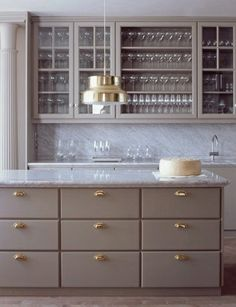 How do we feel about drab kitchens?by alison giese Interiors  I like the brass and the gray marble as contrast to the drab mocha.